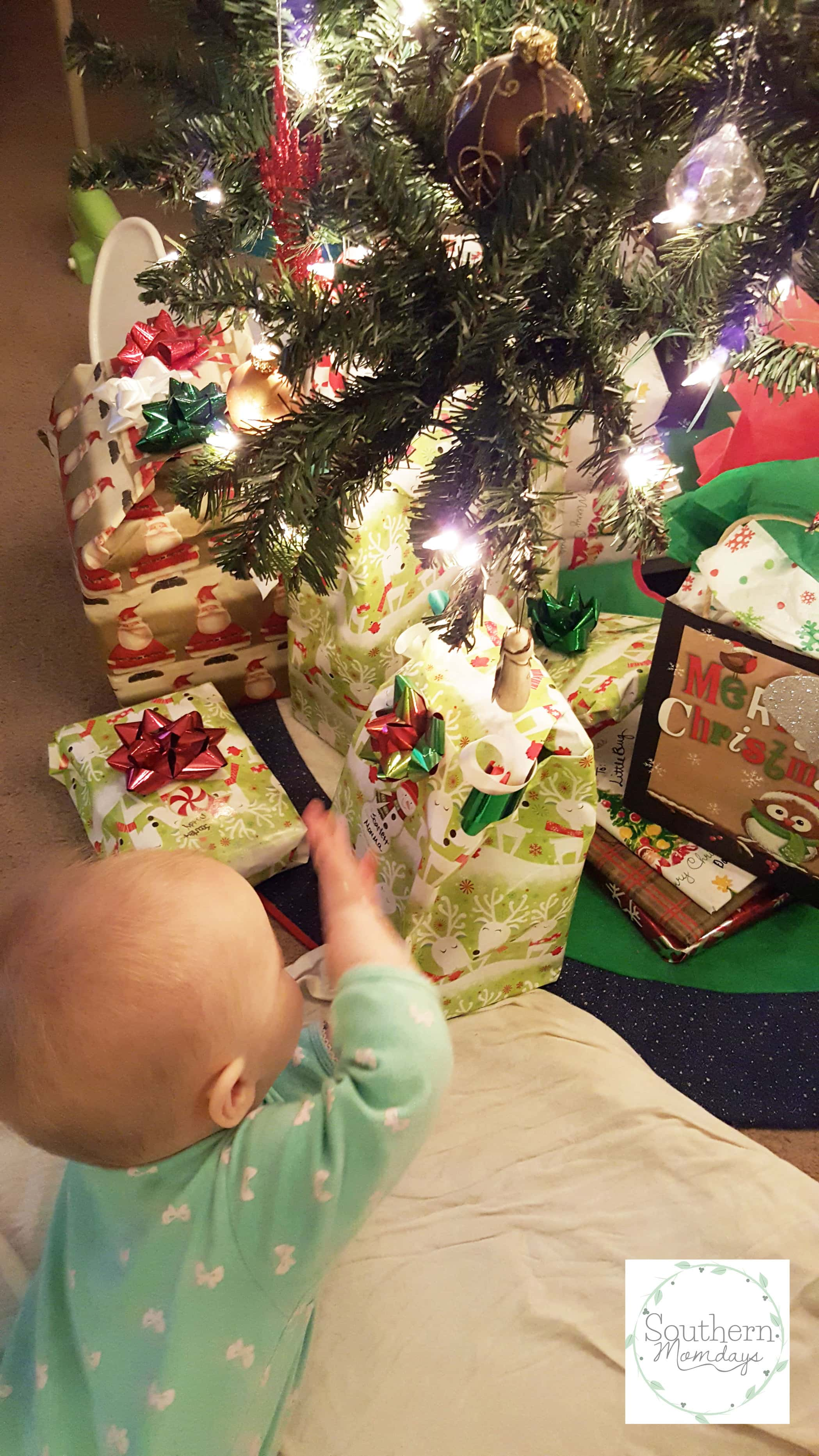 Baby playing with Christmas gifts in How to Save for Christmas (the Easy Way), featured in a holiday budget guide on the Southern Momdays blog
